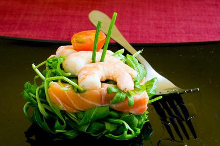 garnishments: fresh salmon tartar on black platter with rocket salad Stock Photo