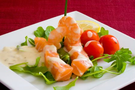 fresh salmon slice on white platter with salad and prawns served with yogurt cream Stock Photo - 1637426