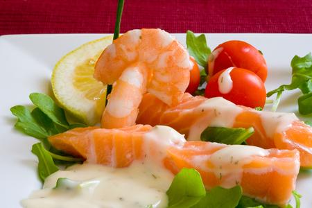 garnishments: fresh salmon slice on white platter with salad and prawns served with yogurt cream