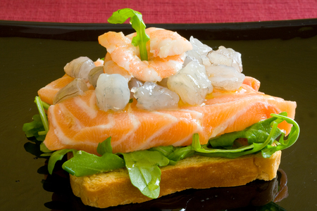 garnishments: fresh salmon slice on a platter with salad and prawns over toast bread