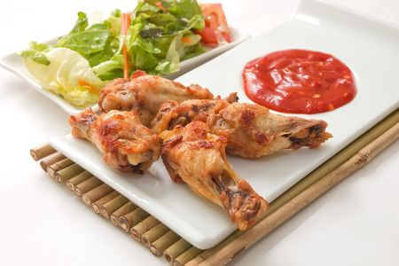 hot spices buffalo wings with salad and chili sauce photo