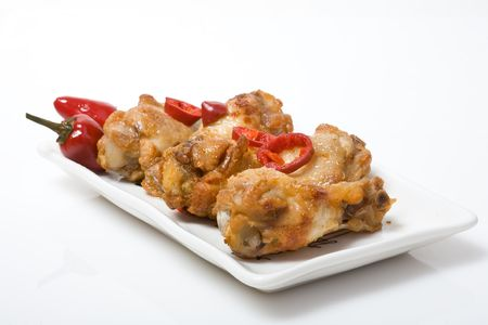 hot spices buffalo wings with very hot red chili peppers photo