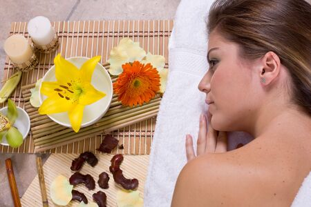 Beautiful young woman  relaxin in spa salon with flowers and candles Stock Photo - 1944370