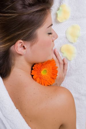 a beautiful woman relaxing in spa salon with flowers and candles photo