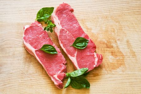 fresh and raw beef steak with green herbs photo