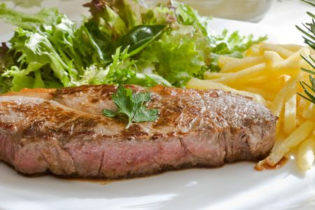 grilled beef steak with green salad and fried photo