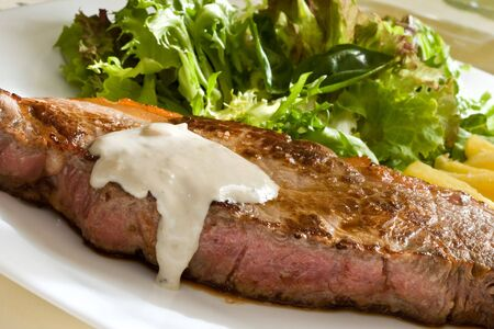grilled beef steak with green salad and blue cheese sauce Stock Photo
