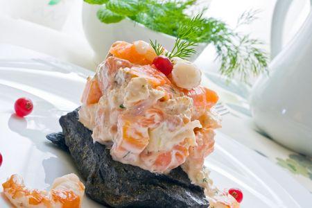 garnishments: prawn and smoked salmon salad with dill sauce over black stone Stock Photo