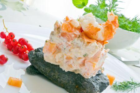 prawn and smoked salmon salad with dill sauce over black stone photo