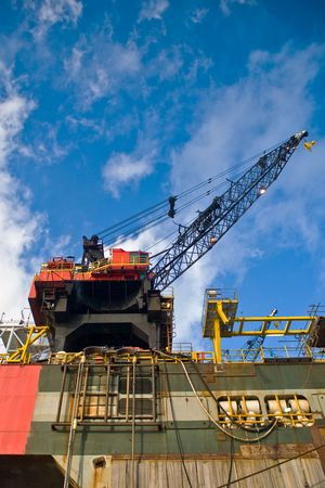 petrochemistry: working crane of an oil rig in harbor