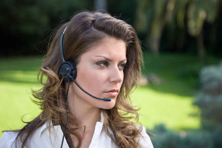 Young and beautiful callcenter operator working outdoor with headset Stock Photo - 2511200