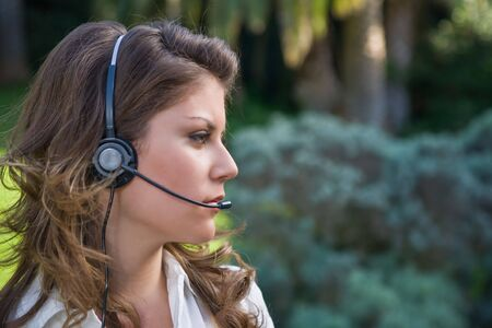 Young and beautiful callcenter operator working outdoor with headset Stock Photo - 2511197