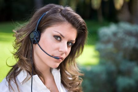Young and beautiful callcenter operator working outdoor with headset photo