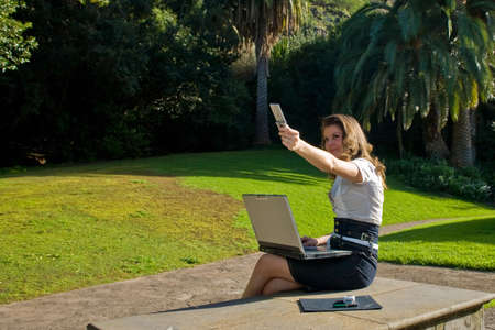 young woman with laptop and phone working at outdoor Stock Photo - 2514261