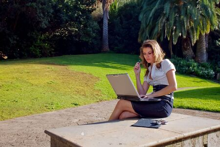 young woman with laptop and phone working at outdoor Stock Photo - 2514262