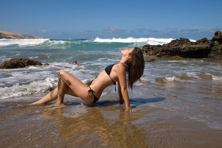 sexy young woman with black bikini in the beach under blue sky