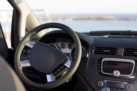 rev: Wheel and dashboard of a car with sea background