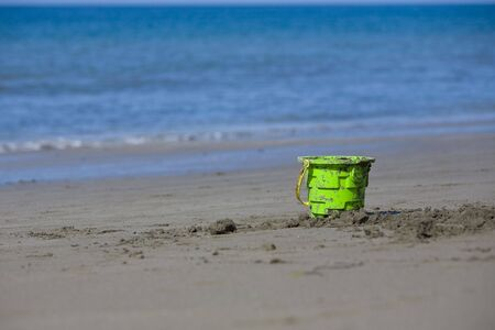 bucket and spade: toy on a sandy beach with the ocean in the background on a sunny day.