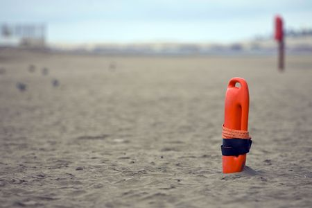 buoyancy: Red plastic buoyancy aid in the sand on lonely beach
