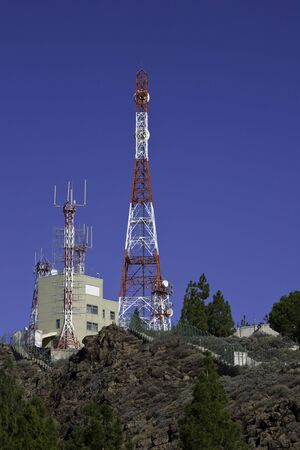 telephonic: telecommunications tower for broadcasting on perfect blue sky