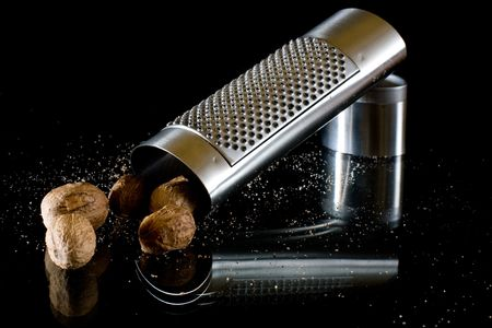 grater: nutmeg and silver grater on black background