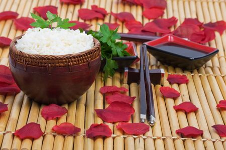 wood rice bowl and chopsticks on bamboo mat photo