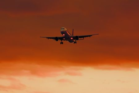 airplane landing at sunset with dark orange clouds background photo