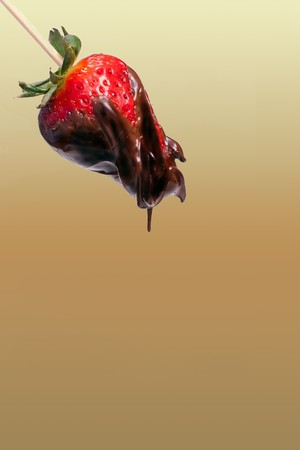 a strawberry dipped on chocolate over mint leaves photo