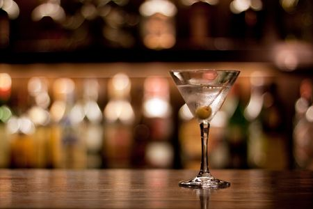 lounge bar: a cup of martini with olive on a old pub