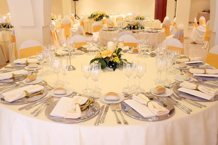 wedding table setting: wedding reception area ready for guests and the party on yellow colors Stock Photo