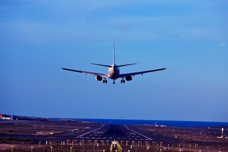 airplane take off: rear view of an airplane landing with blue sky background