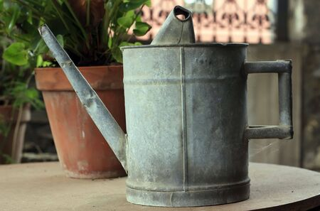 Aged metallic watering can on the garden table photo