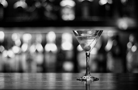 cocktail shaker: a cup of martini with olive on a old pub black and white conversion