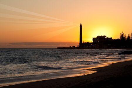 Lighthouse after sunset under orange sky background photo