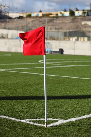 red corner flag on green football field photo