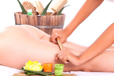 professional masseuse making a bamboo massage in the back in spa
