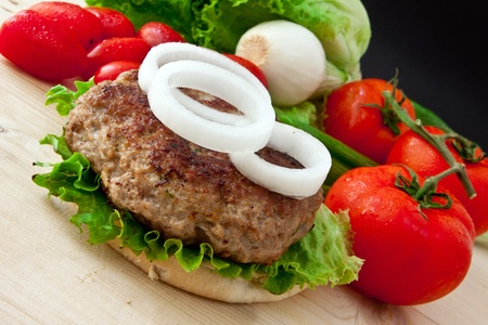 homemade burger with white onion and tomato