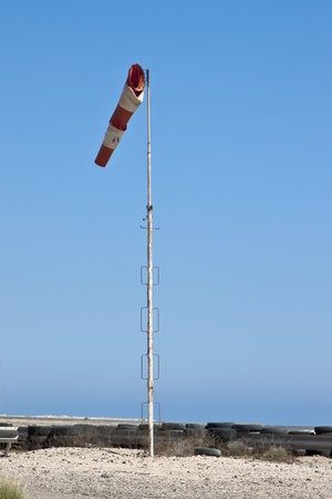 Windsock in airfield showing wind strength on blue sky background photo