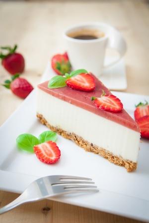 trozo de pastel: un pedazo de queso con fresa en la bandeja blanca Foto de archivo