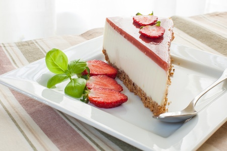a piece of strawberry cheesecake with kiwi fruit photo