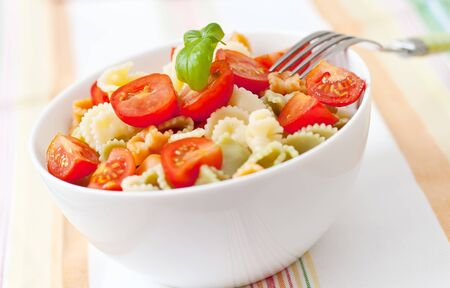 a white bowl of salad pasta with tomato and basil photo