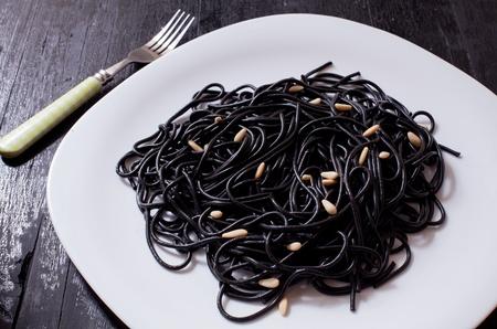 tinted: black tint spaghetti on white tray with fork Stock Photo