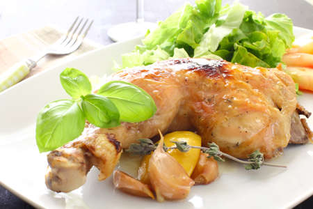 chicken leg: a chicken leg roasted with salad and basil Stock Photo