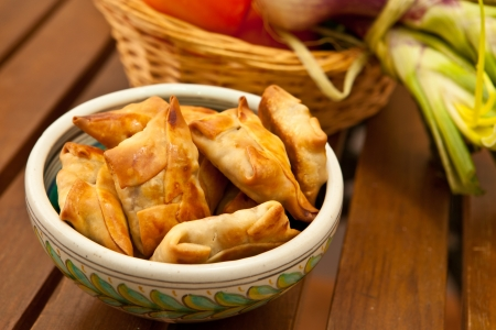 non vegetarian: fried beef samosas with vegetables on bowl Stock Photo