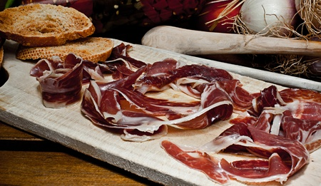 pricey: Spanish red ham table with grilled bread Stock Photo