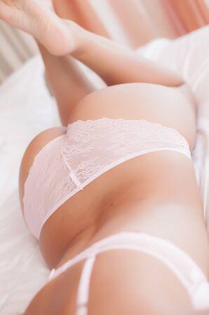 frauenarsch: Frau zur�ck und Esel auf dem Bett mit rosa Dessous