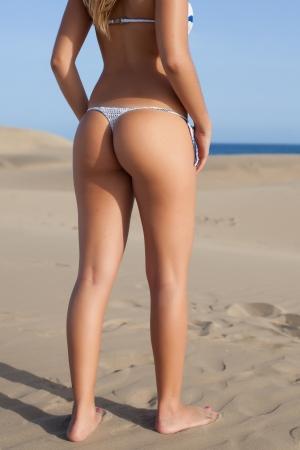 nude female buttocks: young beautiful woman back with bikini on beach Stock Photo
