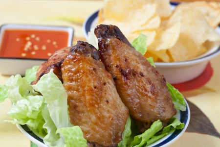 Grilled chicken wings with hot pepper sauce and salad photo