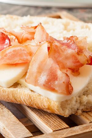 streaky: Crispy bacon baguette with cheese on wooden table Stock Photo