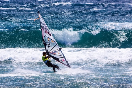 competes: POZO IZQUIERDO, CANARY ISLANDS, GRAN CANARIA - JUL. 11: A professional windsurfer competes at the International PWA Competition on JUL. 09, 2011 in Pozo Izquierdo beach, Gran Canaria. This event is under PWA rules.